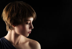 Side portrait of a young woman. With short brown hair and brown glowing eyes Stock Photo