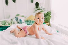 The side porttrait of the cute baby lying on the bed and looking at the camera. stock photography