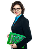 Side pose of a business lady holding calculator. Corporate lady wearing spectacles, holding big green calculator vector illustration