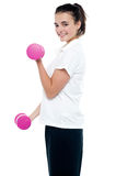 Side pose of girl with dumbbells working out Stock Photo