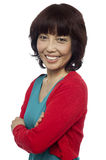 Side pose of smiling asian woman, arms crossed Royalty Free Stock Image