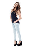 Side pose of woman with hands in pockets. Full length image of a pretty young woman Stock Photography
