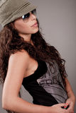Side pose of a woman with sunglasses and cap Royalty Free Stock Image