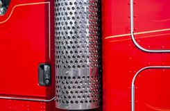 Red big rig semi trucks cab wall and stainless trucks exhaust pipe filter. The side of professional industrial grade cab and wall of classic big rig red clean stock photography