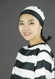Side profile of an Asian young woman smiling in prisoners uniform Stock Photography