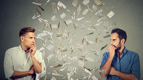 Side profile businessmen looking at each other with money rain in-between. Side profile of two serious businessmen looking at each other with money rain in stock photography