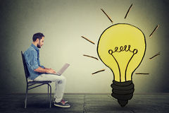 Side profile man using laptop with light bulb on gray wall background Royalty Free Stock Photo