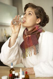Side profile of a mid adult woman drinking a glass of water after her medicine Royalty Free Stock Images