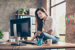 Side profile portrait of attractive beautiful with long hai. R trainee sitting on table at office using working with home computer holding a mouse wearing casual royalty free stock images