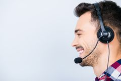 Side profile portrait of a cheerful guy call centre operator in. A headset. He is isolated on a pure light background, smiling royalty free stock photo