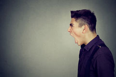 Side profile portrait of young angry man screaming Royalty Free Stock Photos
