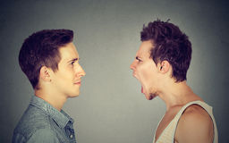 Side profile portrait of young angry man screaming at a calm smiling guy Stock Image