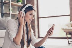 Side profile proto of beautiful lady, listening to music in big. White earphones at home. She is wearing w, sitting on the floor, smiling royalty free stock photo