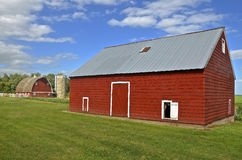 Side profile of a red barn, silo, and granary Royalty Free Stock Images