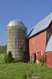 Side profile of a red barn and silo. Stock Photos