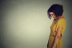 Side profile sad lonely young woman looking down Royalty Free Stock Images