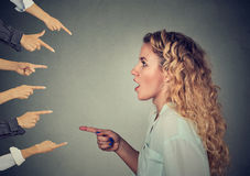Side profile shocked girl pointing against many fingers stock photography