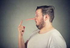 Side profile of a shocked liar man with long nose. Feeling stunned isolated on gray wall background stock photography
