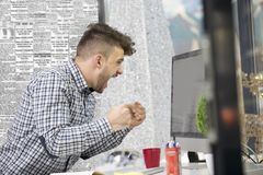 Side profile shot of frustrated young brunet entrepreneur, yelling at his laptop in office and cramps the documents. royalty free stock photo