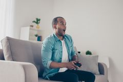 Side profile shot of shocked african young man holding joystick. And playing videogames. He is very excited, sitting on couch at home stock photos