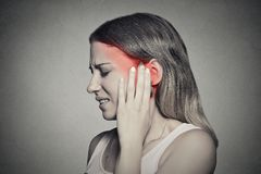 Side profile sick female having ear pain touching painful head royalty free stock photo