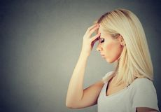 Sorrowful sad woman thoughtful with worried face expression. Side profile of a sorrowful young sad woman thoughtful with worried face expression royalty free stock photos