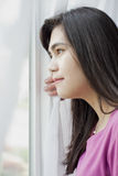 Side profile of teen girl looking out window Royalty Free Stock Images