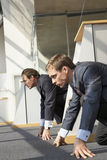 Side profile of two businessmen crouching at a starting line stock photos