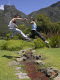 Side profile of two young men jumping over a stream Stock Images