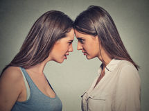 Side profile unhappy young female friends looking at each other Stock Photos