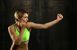 Side profile view of young athletic women boxing. Close up side view profile portrait of one young athletic woman shadow boxing in sportswear in gym over dark stock images