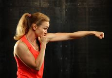 Side profile view of young athletic women boxing. Close up side view profile portrait of one young middle age athletic woman shadow boxing in sportswear in gym stock image