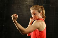 Side profile view of young athletic women boxing. Close up side view profile portrait of one young middle age athletic woman shadow boxing in sportswear in gym royalty free stock image