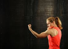 Side profile view of young athletic women boxing. Close up side view profile portrait of one young middle age athletic woman shadow boxing in sportswear in gym royalty free stock photography