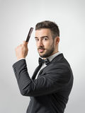 Side profile view of young man combing hair looking at camera Royalty Free Stock Photo