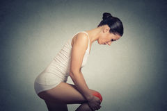 Side profile woman standing holding lifting  her painful knee colored in red Royalty Free Stock Photography