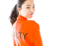 Side profile of a young Asian woman looking back in prisoners uniform Stock Photo