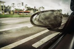 Side Rear View Mirror on Cloudy Day. Wet e Rear View Mirror on Cloudy Day from Moving Car Royalty Free Stock Image