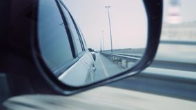 Side rear-view mirror on a modern car. Stock. View from the car window to the mirror. The concept of travelling by car.  stock footage