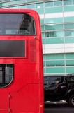 Side of Red London Double Decker Bus and Black Car. A red double decker bus passes a black car outside a green glass building in London Stock Image