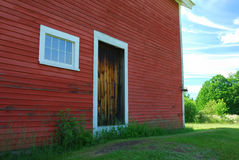 Side of red wood barn with wooden door and 8 pane window. White trim blue sky Stock Image