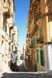 Side street in historic city. Tall buildings in a side road in the city of Valetta, capital of Malta Stock Photography