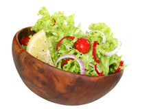 Side Salad. ~ wooden salad bowl with curly coral lettuce, tiny grape tomatoes, red onion, capsicum, lemon and herbs Royalty Free Stock Images