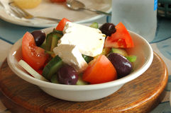 Side salad. A delicious fresh healthy colorful Greek side salad with tomatoes, feta cheese, cucumber, onions and black olives in a white bowl on a wooden board Royalty Free Stock Photos