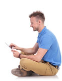 Side of a seated man working on a tablet Royalty Free Stock Photography