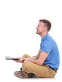 Side of a seated young man holding a book Royalty Free Stock Photo
