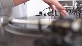 Side shot of an audio mixer and a vinyl rotating, a DJ is scratching on the vinyl.  stock footage