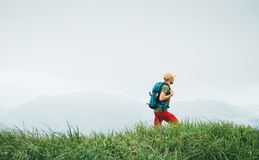 Side shot of hiker man walking by the foggy cloudy weather mountain range path with backpack. Active sport backpacking healthy royalty free stock photo