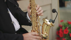 Side Shot of Male Playing Saxophone in The Street. Close-Up on Fingers Pressing the Keys of the Instrument. Musician Playing the Saxophone in the Street. the stock video footage