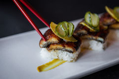 Side Shot of Sushi Picked Up With Red Chopsticks. Royalty Free Stock Image